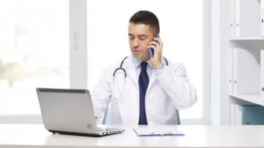 Happy doctor with laptop calling on smartphone — Stock Video