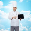 Happy male chef cook showing tablet pc — Stock Photo #71194557