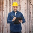 Smiling male builder in helmet with clipboard — Stock Photo #71194849
