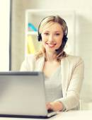 Friendly female helpline operator with laptop — Stock Photo