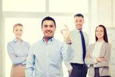 Empresário sorridente mostrando sinal de ok no escritório — Fotografia Stock