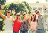 Group of smiling friends waving hands outdoors — Stock Photo
