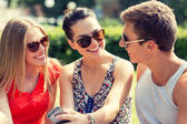 Smiling friends with smartphone sitting in park — Stock Photo