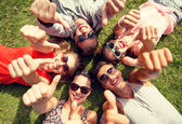 Smiling friends showing thumbs up lying on grass — Stock Photo