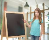 Happy little girl with blackboard and chalk — Stock Photo