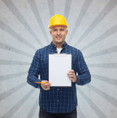 Smiling male builder in helmet with clipboard — Stock Photo