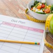 Close up of diet plan and food on table — Stock Photo #71417781