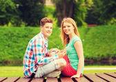 Uśmiechający się para z smartphone i słuchawki — Zdjęcie stockowe