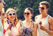 Group of smiling friends with ice cream outdoors — Stock Photo
