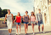 Group of smiling friends walking in city — Stock Photo