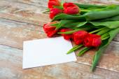 Close up of red tulips and blank paper or letter — Stock Photo