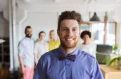 Happy young man over creative team in office — Stock Photo