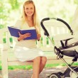 Happy mother with book and stroller in park — Stock Photo #71588927