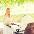 Happy mother with stroller in park — Stock Photo #71589167