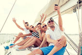 Smiling friends sitting on yacht deck — Stok fotoğraf