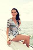 Smiling young woman sitting on yacht deck — Stock Photo