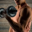 Close up of young man with dumbbell flexing biceps — Stock Photo #71590611