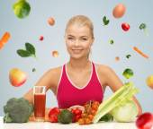 Happy woman with vegetarian food and vitamins — Stock Photo