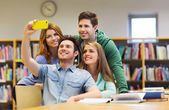 Students with smartphone taking selfie in library — Stock Photo