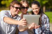 Students or teenagers with tablet pc taking selfie — Stock Photo
