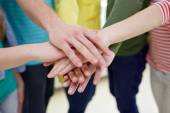 Close up of students or friends with hands on top — Stock Photo