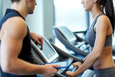 Close up of woman with trainer on treadmill in gym — Stock Photo