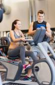 Happy woman with trainer on exercise bike in gym — Stock Photo