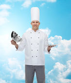 Happy male chef cook opening cloche — Stock Photo
