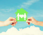 Hands holding green house with family — Stock Photo