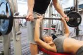 Man and woman with barbell flexing muscles in gym — Stock Photo