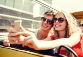 Smiling couple with smartphone making selfie — Stock Photo