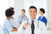Happy doctor over group of medics at hospital — Stock Photo