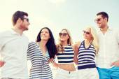 Smiling friends in sunglasses talking on beach — Stock Photo