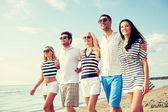 Smiling friends in sunglasses walking on beach — Stock Photo