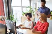 Happy creative team with computer in office — Stock Photo