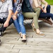 Close up of many legs sitting on bench at park — Stock Photo #72153867