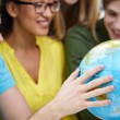 Group of smiling students looking at globe — Stock Photo #72155071