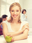 Beautiful girl with green apple at school — Stock Photo
