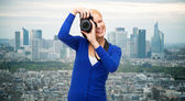 Smiling woman taking picture with digital camera — Stock fotografie