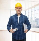 Smiling male builder in helmet with blueprint — ストック写真