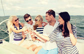 Smiling friends with glasses of champagne on yacht — ストック写真