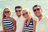 Smiling friends sitting on yacht deck — ストック写真