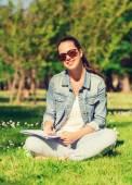 Leende ung flicka med anteckningsboken i park — Stockfoto