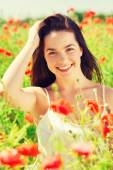 Smiling young woman on poppy field — ストック写真