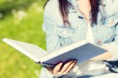 Close up of young girl with book in park — ストック写真