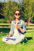 Leende ung flicka med anteckningsboken och kaffe kopp — Stockfoto