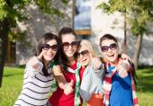 Happy teenage girls showing thumbs up at campus — Stock Photo