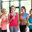 Women with bottles of water in gym — Stock Photo #72301137