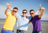 Happy friends with beer bottles on beach — Stock Photo