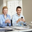 Smiling business people with smartphones in office — Stock Photo #72509383